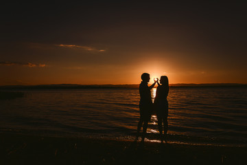 a guy and a girl make a heart out of their hands on the sea at sunset