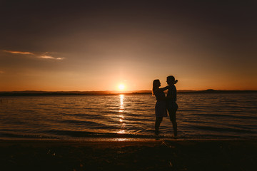 guy and girl hugging the sea at sunset