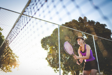 Close up image of a female tennis player playing tennis on a court in bright sunlight