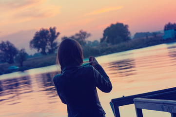 Girl takes pictures near the lake at the sundown