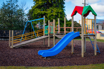 A colourful children's playground with slide and fort and bark chips on the ground