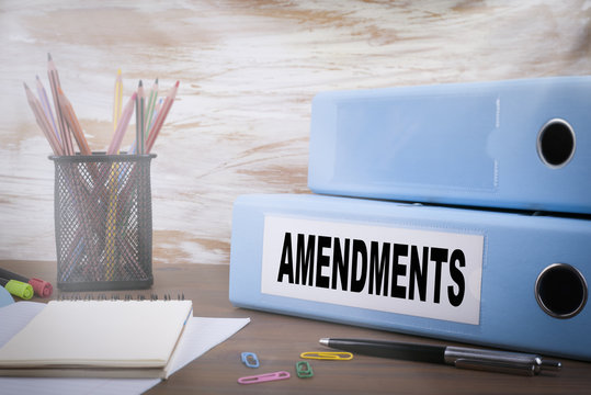 Amendments. Office Binder on Wooden Desk. On the table colored pencils, pen, notebook paper