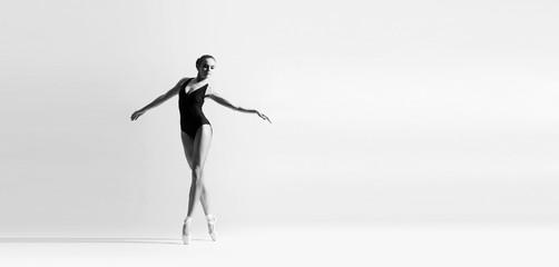 Graceful ballerina dancing in art performance. Young and beautiful ballet dancer.