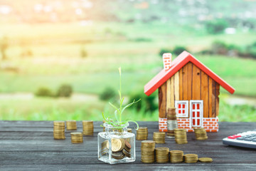 wooden house model and step of coins with plant growing,saving and investment planning concept
