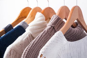 Knitted sweaters on hangers close-up