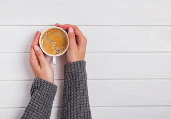 Fotobehang - Woman's hands in knitted sweater holding a cup of coffee on the white wooden background