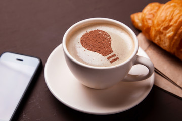 Cup of coffee with the idea of a light bulb on the foam. Coffee gives new ideas and creativity. Morning coffee
