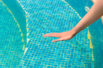 Young girl testing the swimming pool temperature with her hand in the water