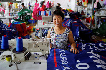 """A worker poses for pictures as she makes flags for U.S. President Donald Trump's """"Keep America Great!"""" 2020 re-election campaign at Jiahao flag factory in Fuyang"""