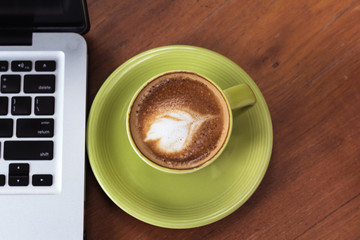 coffee cup and computer laptop on wooden table