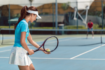 Side view of a beautiful and competitive woman smiling, while holding the tennis racket and the ball before starting the match on a professional tennis court