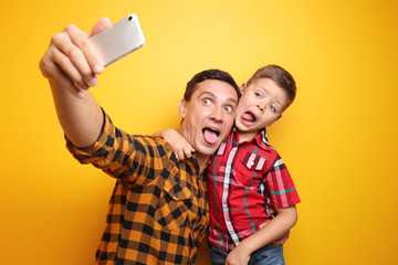 Little boy and his dad taking funny selfie on color background