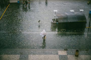 Gens dans rue pavée  sous la pluie