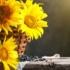 Fototapete - Beautiful sunflowers in a basket on a wooden table.