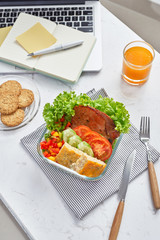 Healthy food. Lunch box with diet meal on workplace, flat lay of desktop with foiled container