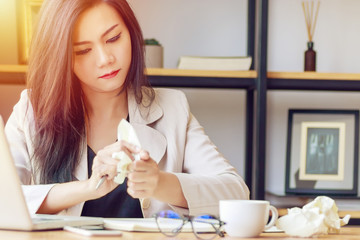 Asian businesswoman stressed with unsuccessful work, squeeze paper in hand sitting at office desk covered with crumpled paper and feeling tired after work fail, give up, no idea