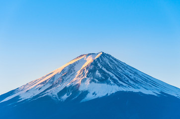 Close-up of Mount Fuji view with Lake Kawaguchi and clear blue sky background in Kawaguchiko, Japan Peak of Fuji mountain cover with snow and shading with golden sunlight in the morning