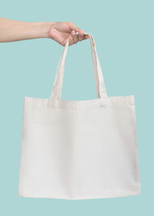 Tote bag canvas white cotton fabric cloth for eco shoulder shopping sack mockup blank template isolated on pastel green or blue mint background (clipping path) with woman's handling hand