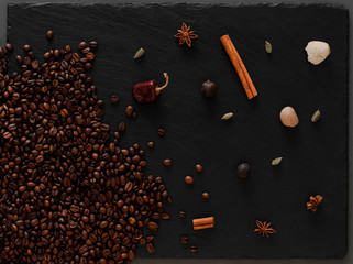 Coffee beans flatlay. Warm photo with coffee beans and spices on dark texturised background.