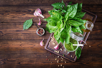 Homemade pesto sauce fresh basil, pine nuts and garlic on wooden background. Italian food. Top view. Flat lay