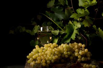 виноград жёлтый спелый и бокал с вином стоят на столе