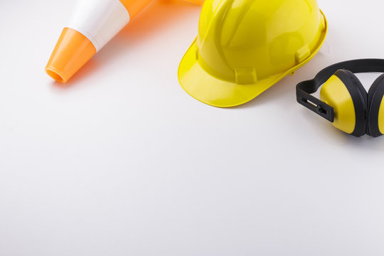 Traffic Cone, Hardhat, and Earmuffs on White Background with Copy Space