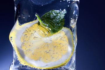 A slice of lemon and mint in a glass of water.