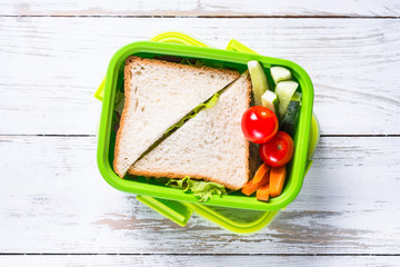 Lunch box with sandwich and vegetables.