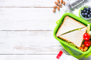 Lunch box with sandwich, vegetables, water, nuts and berries.