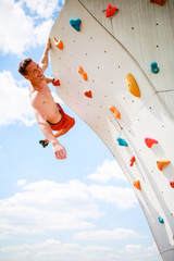 Photo of smiling athlete man looking at camera practicing on wall for rock climbing against blue sky with clouds