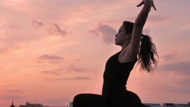 Yogi girl is changing poses from one legged downward-facing dog to warrior one on rooftop in summer on sunset, healthy lifestyle, relax concept, sport concept