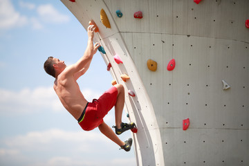 Photo of sportsman exercising on wall for climbing against cloudy sky