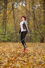 Full-length picture of female athlete jumping with rope at autumn forest