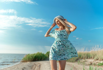 a girl in a blue dress strolls along the seashore