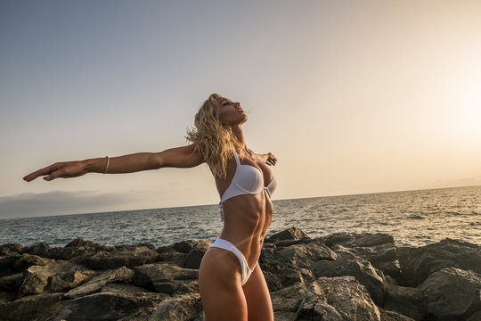 enjoying happiness and outdoor ocean summer vacation lifestyle for beautiful blonde young model woman opening arms and feel and breathe the sea energy. perfect body and sexy girl