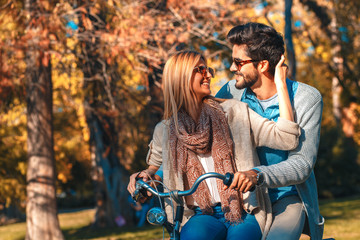 Happy young couple having fun riding a bicycle on sunny day in the park.