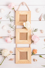 Poster three wooden frame mockup, top view, pink roses on white wooden background. Holiday Wedding, Birthday, Mother's, Valentines, Women's Day concept. Flat lay. Copy space