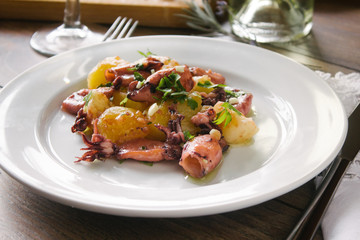 Alluring dish made of grilled squid and baked potatoes. Close up.