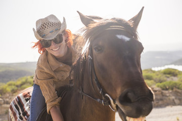 beautiful cheerful young woman enjoy and ride her brown cute horse in friendship and relationship. animal lover and pet therapy concept. travel and vacation alternative lifestyle