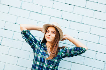 Beautiful teenage girl in hat smile outdoors, with blue brick wall background