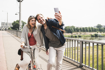 Happy couple taking a selfie on a bridge