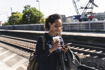 Young woman at train station reading text messages on her phone