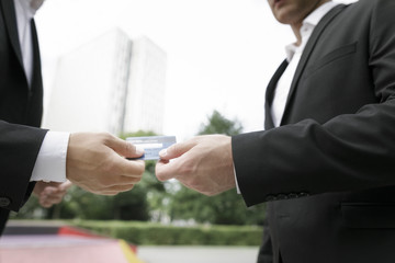 Two businessmen handing over credit card