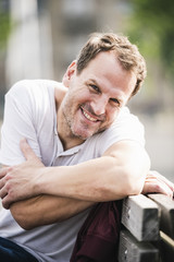 Portrait of smiling man sitting on bench