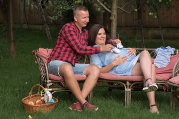 Young adult male and pregnant woman amuse themselves in the garden