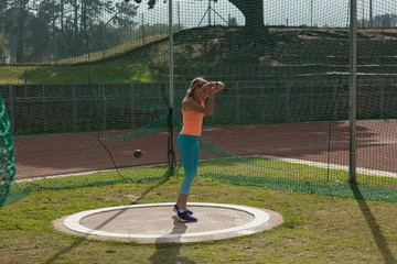 Female athlete practicing shot put