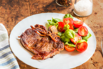 Delicious fried steak with fresh salad of spinach and cherry tomatoes in a white plate on a rustic table