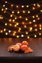 Mandarins and Cinnamon on Background of Blurred Defocused Multicolor Lights