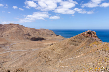 Typical landscape of Fuerteventura with barren volcanic mountains and the ocean - a view from the Entallada lighthouse terrace