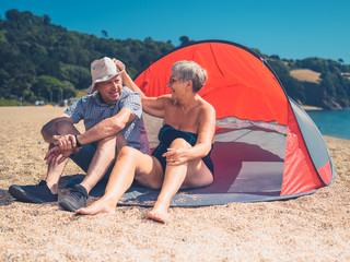 Senior couple sitting in beach shelter